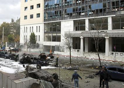Bomberos y policías inspeccionan la zona en la que ha estallado la bomba, frente a los tribunales de justicia de asuntos administrativos, este jueves, en Atenas.