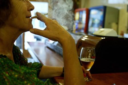 Una mujer fuma mientras toma una consumición en la barra de un bar.