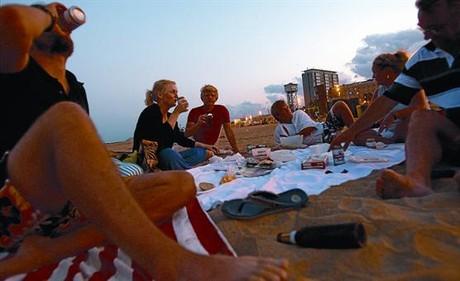 Un grupo de jóvenes cena y consume alcohol en la Barceloneta, la semana pasada.