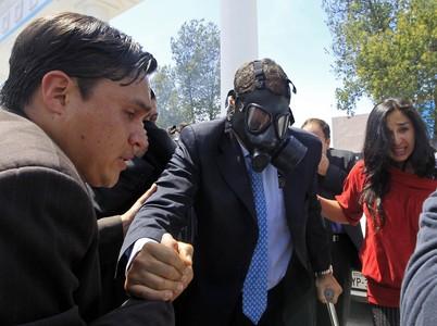 El presidente de Ecuador, Rafael Correa, sale con máscara de gas de una reunión con la policía, en la que ha sido increpado y le han lanzado gas lacrimógeno, hoy, en Quito.