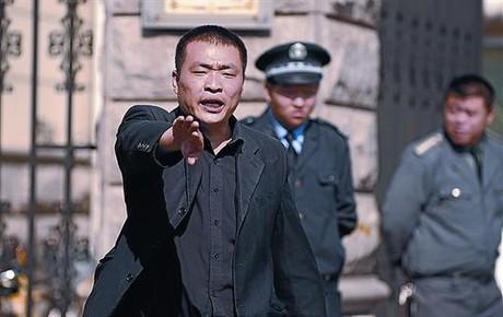 Un policía impide tomar fotos ante la casa de la mujer de Liu Xiaobo.