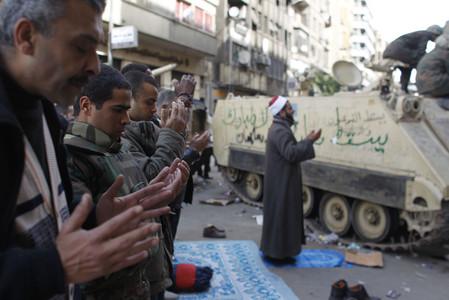 Participantes en los enfrentamientos entre partidarios y opositores al régimen de Hosni Mubarak rezan junto a un tanque del Ejército en el centro de El Cairo.