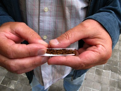 Un caballero se lía un cigarro con picadura.